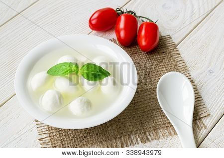 Mini Mozzarella Cheese Balls With Brine, Three Red Cherry Tomatoes And Porcelain Spoon On A  White R