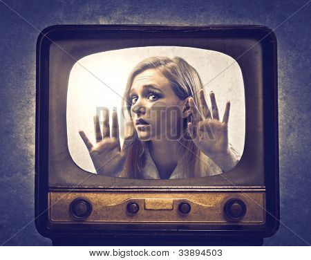 Young woman pressed against the glass of a television