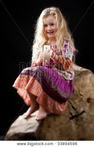 Cute little girl playing tamburine while sitting on a trunk, studio shot