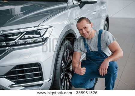 Job Well Done. After Professional Repairing. Man Looking At Perfectly Polished Silver Colored Car.