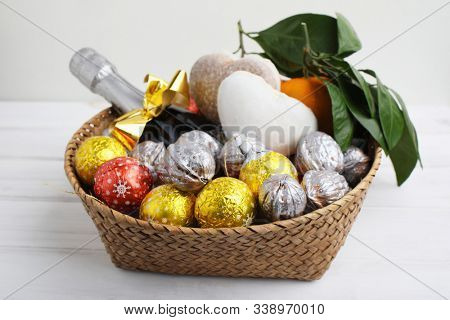 Christmas gift basket with chocolate candies, walnuts, gingerbread, mandarin oranges, and a bottle of champagne