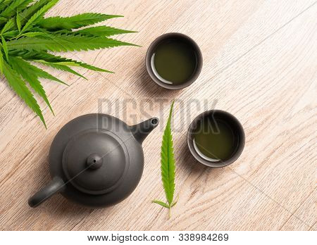 Tea Made From Cannabis Leaves ,a Glass Of Hot Marijuana Tea On Wooden Table , Tea Pot And Cups On Wo