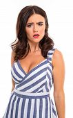 indignant european brunette girl in a striped elegant dress with a neckline on a white wall. poster