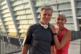 Powerful Couple. Portrait Of Happy Middle-aged Man And Woman In Sport Clothing Looking At Camera Wit