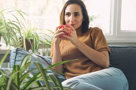 Beautiful Woman Relaxing At Home With Tea. Woman Relaxing On Couch At Home. Hipster Lifestyle. Beaut