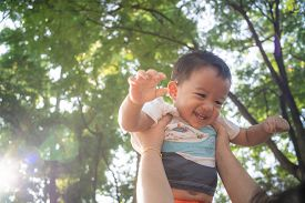 Mom Lifting Hold Infant Baby Boy In City Park Against Sun Light