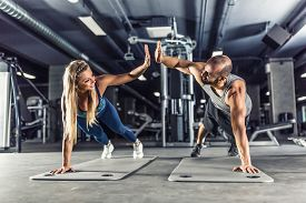 Sport Couple Doing Plank Exercise Workout In Fitness Centrum. Man And Woman Practicing Plank In The