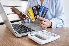 Businesswoman Using Smartphone, Laptop And Holding Credit Card For Paying Detail Page Display Online