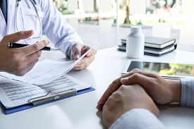 Doctor Presenting With Patient And Checking Results On Report And Prescription About The Problem Of