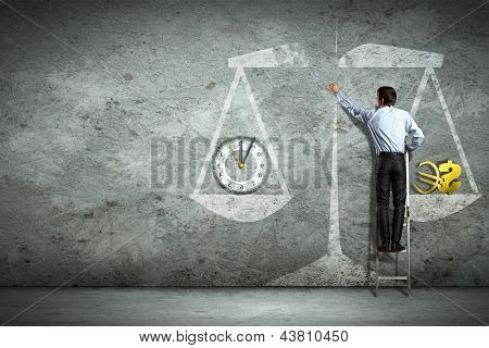 Businessman on ladder pointing at scale picture