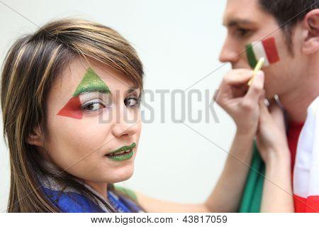 Italian football fans putting on facepaint