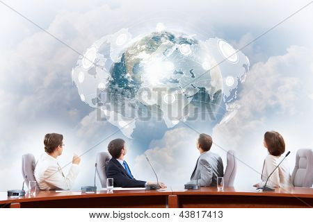 Image of businesspeople at presentation looking at virtual project. Elements of this image are furnished by NASA