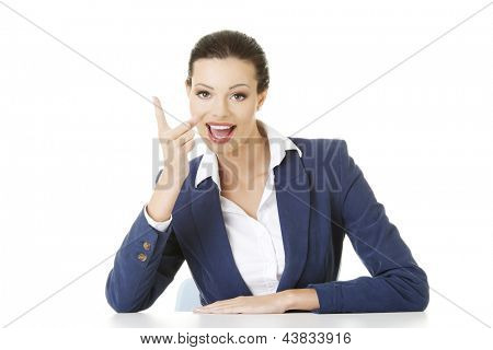 Business woman sitting at the desk and pointing with finger to empty copy space, isolated over white background