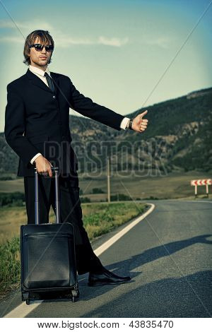 Handsome business man standing on a highway and catching a car.