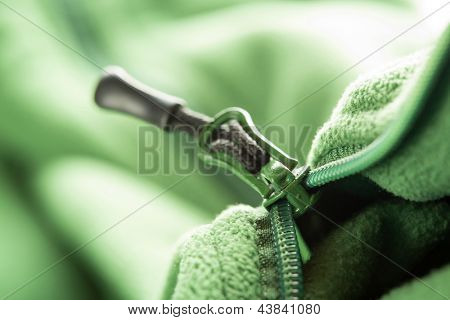 Closeup of zipper opening green fleece jacket