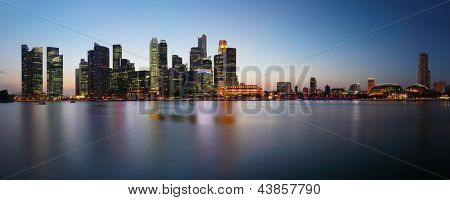 Panorama of a big city with tall buildings reflected in a water. Singapore