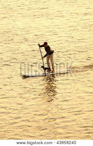 man paddleboarding at sunset with dog
