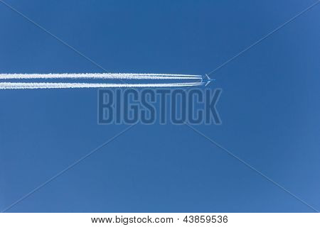 a plane with contrails in the blue sky. longing for your next vacation!