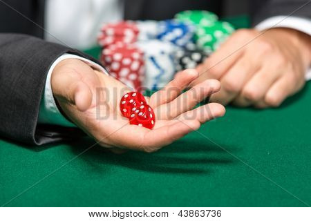 Player throws dices on the poker table. Addiction to the gambling