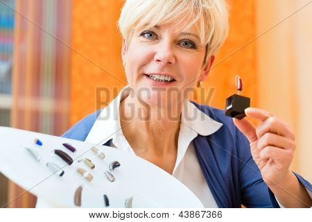 Older woman or female pensioner with a hearing problem make a hearing test and may need a hearing aid, she looking on a selection of them