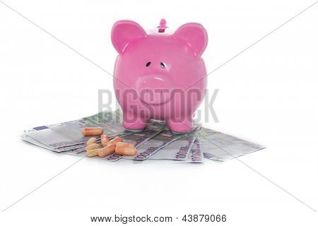 Piggy bank on pile of dollars with tablets on white background