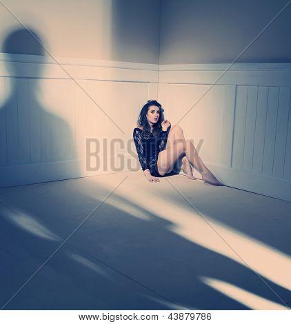 sad woman sitting alone in a empty room