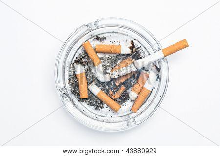 Overhead of burning cigarette in ashtray on white background