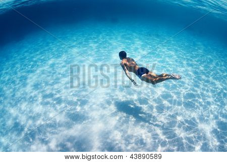 Young man diving on a breath hold in a tropical sea over sandy bottom