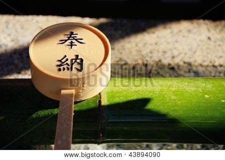 Scoop set atop a ritualistic tsukubai hand-washing basin with Japanese Kanji charachters reading