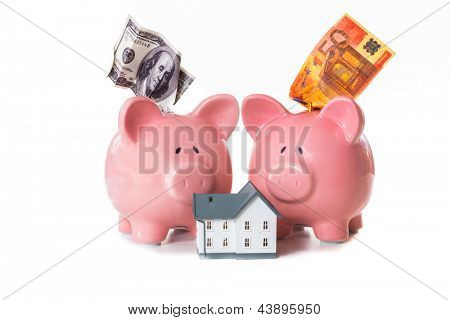 Dollar and euro notes sticking out of piggy banks with model home on white background