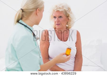Home nurse showing a pill bottle to her patient at home