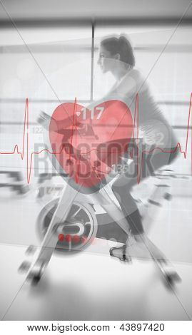 Woman on exercise bike with futuristic interface show ing heartbeat