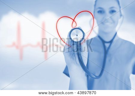 Happy nurse holding up stethoscope to heart design in blue tint on background of blue sky and ECG line