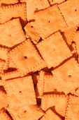 Close up of a group of orange cheese crackers. poster