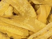 Close-up of thin plantain slices dried to crispy chip-like texture eaten with salsa or dip. poster