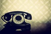 vintage old telephone, black retro phone is on wooden table over green old-fashioned wallpaper poster