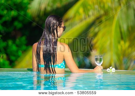 Rear View Of Young Beautiful Woman Enjoying The Luxury Quiet Swimmingpool