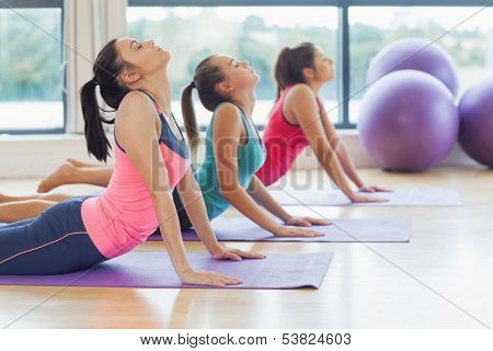 Side view of trainer with class doing the cobra pose in bright fitness studio