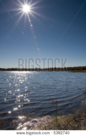 Sun Over Lake With Lens Flare