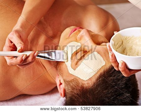 Man with clay facial mask in beauty spa. poster