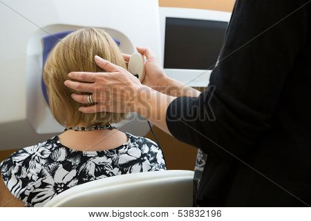 Midsection of optician adjusting female patient's head for retinal checkup