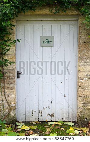 No entry sign on weathered garden door