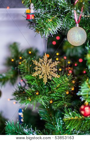 Snowflake on a Christmas tree with multi-colored fairy lights