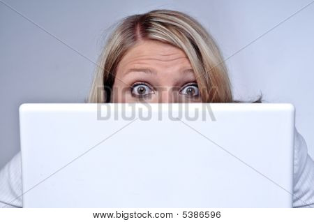 Blond Woman Looking Behind Laptop