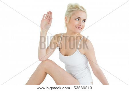 Toned young woman in the Ardha Matsyendrasana position against white background