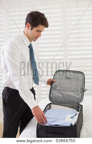 Side view of a businessman unpacking luggage at a hotel bedroom