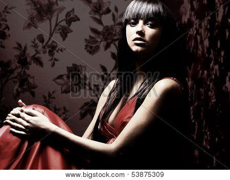 Beautiful woman seated in dark room