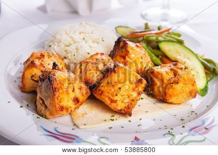 Zesty Chicken Shish Kebabs Served On A Lavash Bread With Rice Pilaf