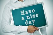 man holding a chalkboard with the sentence have a nice day written in it poster