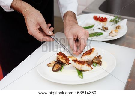Chef is cooking a fish dish with vegetables and mushrooms